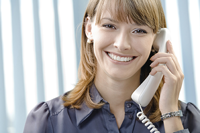 Portrait of happy businesswoman with phone at office