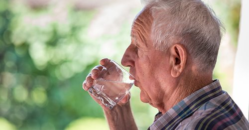 Senior man drinking water outside to reduce symptoms of dehydration